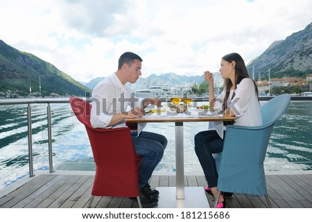 happy young couple having lanch at beautiful restaurant on the beach