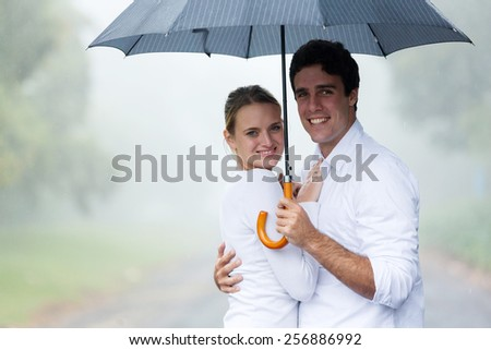 happy young couple holding an umbrella in the rain - stock photo