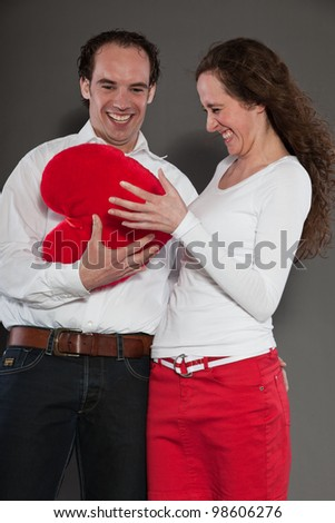 Happy young couple holding big red heart isolated on grey background. Fashion style studio portrait.