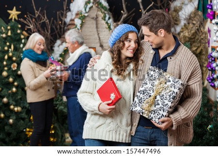 Happy young couple holding Christmas presents with parents standing in background at store - stock photo