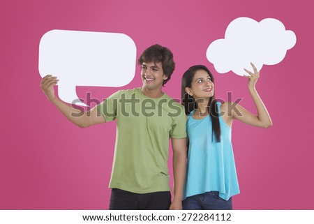 Happy young couple holding communication bubbles over pink background - stock photo