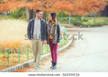 Happy young couple holding hand and talking while walking in a park  - stock photo
