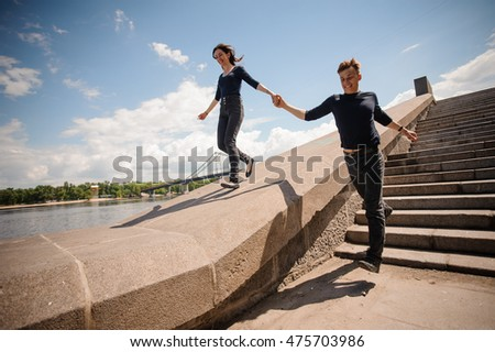 Happy young couple holding hands and running down the stairs