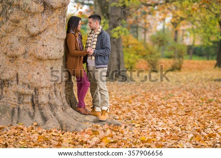 Happy young couple holding hands while walking through park in autumn - stock photo
