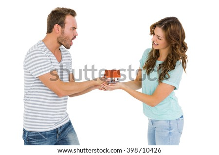 Happy young couple holding model house on white background - stock photo