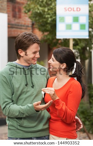 Happy young couple holding new home key with sold sign in background