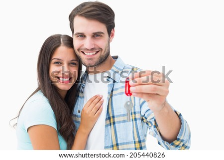 Happy young couple holding new house key on white background - stock photo