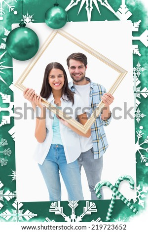 Happy young couple holding picture frame against christmas frame - stock photo