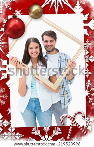 Happy young couple holding picture frame against christmas themed page - stock photo
