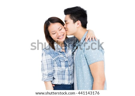 Happy young couple hugging and kissing on white background - stock photo