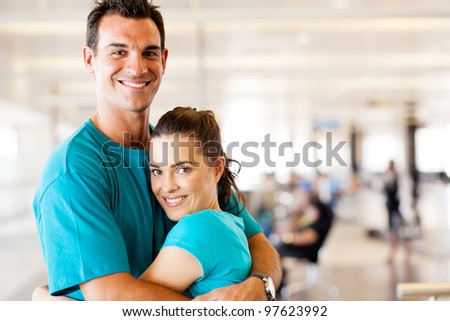 happy young couple hugging at airport