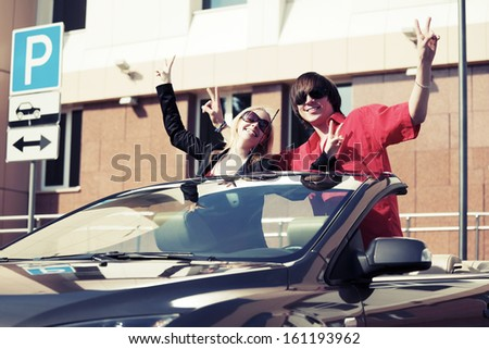 Happy young couple in a car - stock photo