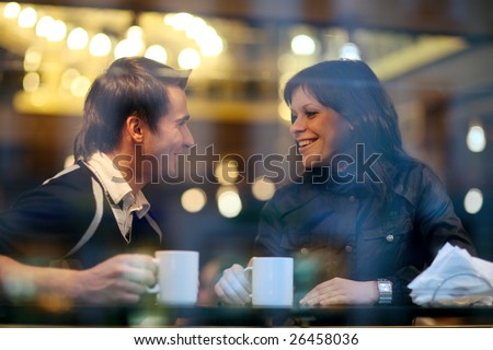 Happy young couple in cafe, having a great time together. View through cafe window.