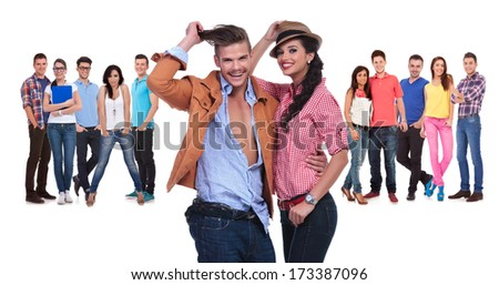 happy young couple in front of a large team of casual people on white background - stock photo