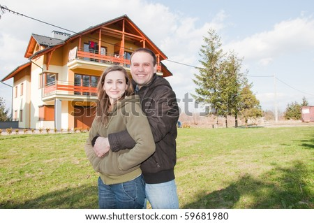 happy young couple in front of house - stock photo