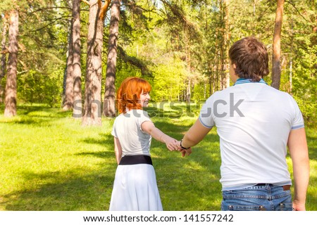 Happy Young Couple in Green Summer Sunny Park having fun together, holding hands. Family outdoors, love, leisure together concept.