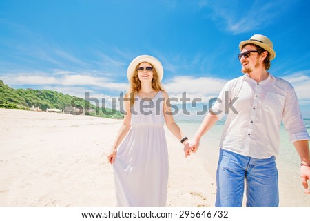 Happy young couple in hats and sunglasses walk at tropical beach with white sand against beautiful view on background. Lovers in full body length on beach.  - stock photo
