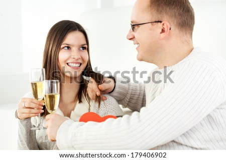 Happy Young couple in home interior enjoying in glass of champagne. - stock photo