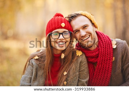 Happy young couple in leaf fall enjoying autumn - stock photo
