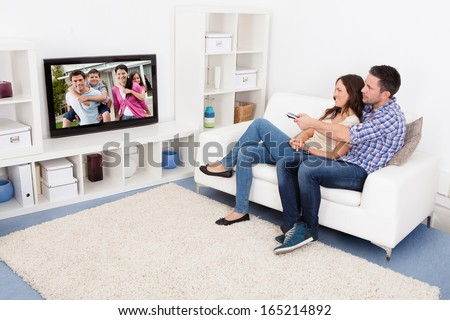 Happy Young Couple In Livingroom Sitting On Couch Watching Television