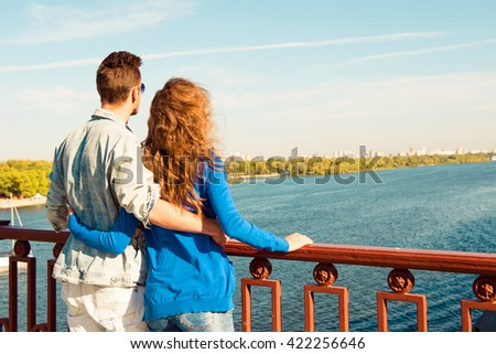 Happy young couple in love embracing each other on the bridge - stock photo