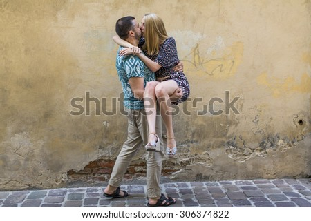 Happy young couple in love having fun against the wall of the house. - stock photo
