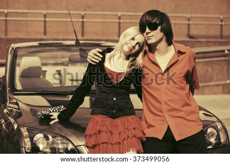 Happy young couple in love next to car - stock photo