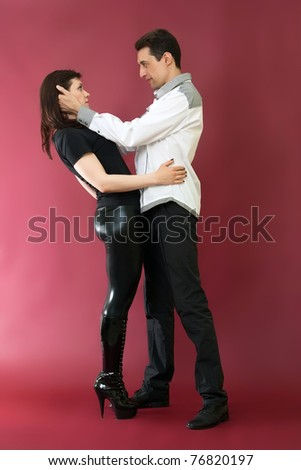 Happy young couple in love on red burgundy background - stock photo