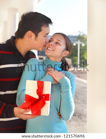 Happy young couple in love with present outdoors