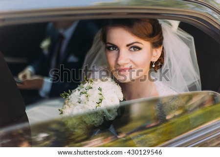Happy young couple in luxurious car after their wedding. Focus on beautiful bride, smiling at camera - stock photo