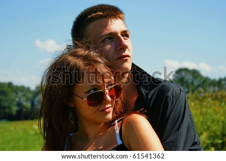 Happy young couple in summer time sitting on a meadow.