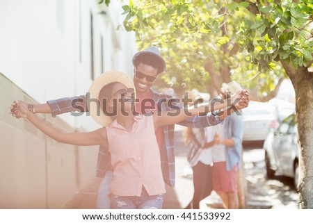 Happy young couple in sunglasses dancing on road - stock photo