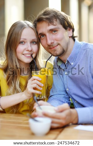 Happy young couple in the outdoor cafe  - stock photo