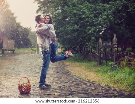 Happy young couple in Ukrainian style clothes hugging under rain - stock photo