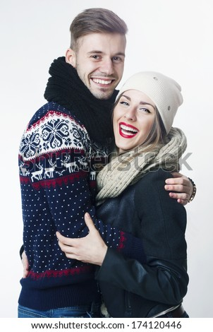 Happy Young Couple in Winter clothes having fun. Isolated in studio. - stock photo