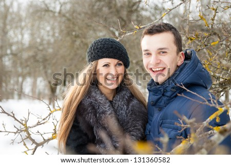 Happy Young Couple in Winter garden embracing