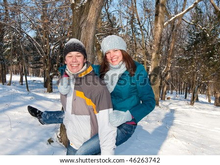 Happy, young couple is laughing while they play in the snow. Looking at the camera