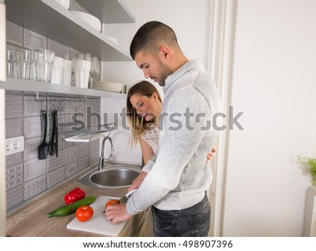Happy young couple is preparing healthy meal together in the kitchen. Young man is slicing vegetables on the kitchen counter and smiling young woman is looking what he is doing.