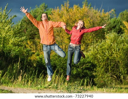Happy Young Couple - jumping in the sky above a orange-green tree - stock photo