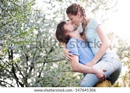 happy young couple kissing outdoor in the park  - stock photo