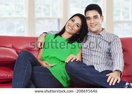 Happy young couple laughing and looking at camera in a living room - stock photo