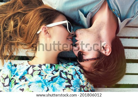 Happy young couple laying on white floor and have a sweet kiss, wearing retro clothes and sunglasses. - stock photo