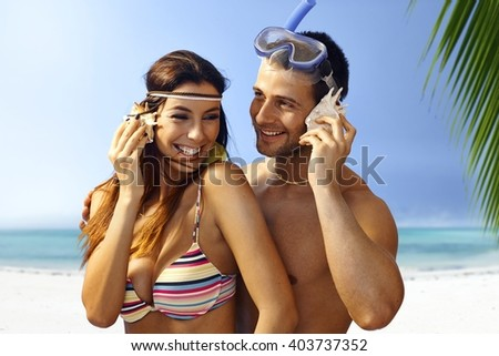 Happy young couple listening to murmur of sea in seashell on the beach, smiling, hugging.