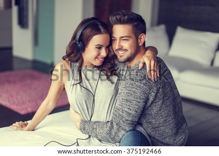 Happy young couple listening to music indoor, cuddle each other - stock photo
