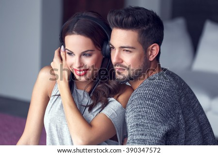 Happy young couple listening to music indoor, teeth smile - stock photo