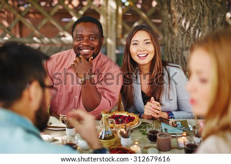 Happy young couple looking at camera by Thanksgiving table - stock photo