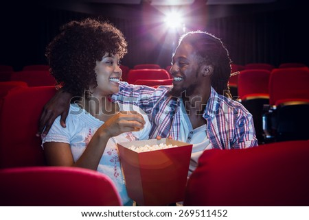 Happy young couple looking at each other at the cinema