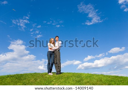 Happy young couple looking at something above a green meadow