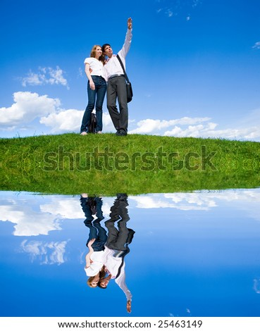 Happy young couple looking at something above a green meadow. Man show something by hand - stock photo