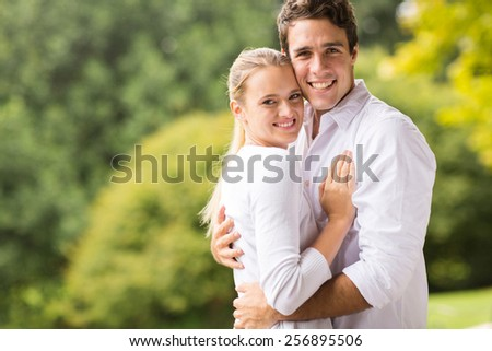 happy young couple looking at the camera outdoors - stock photo